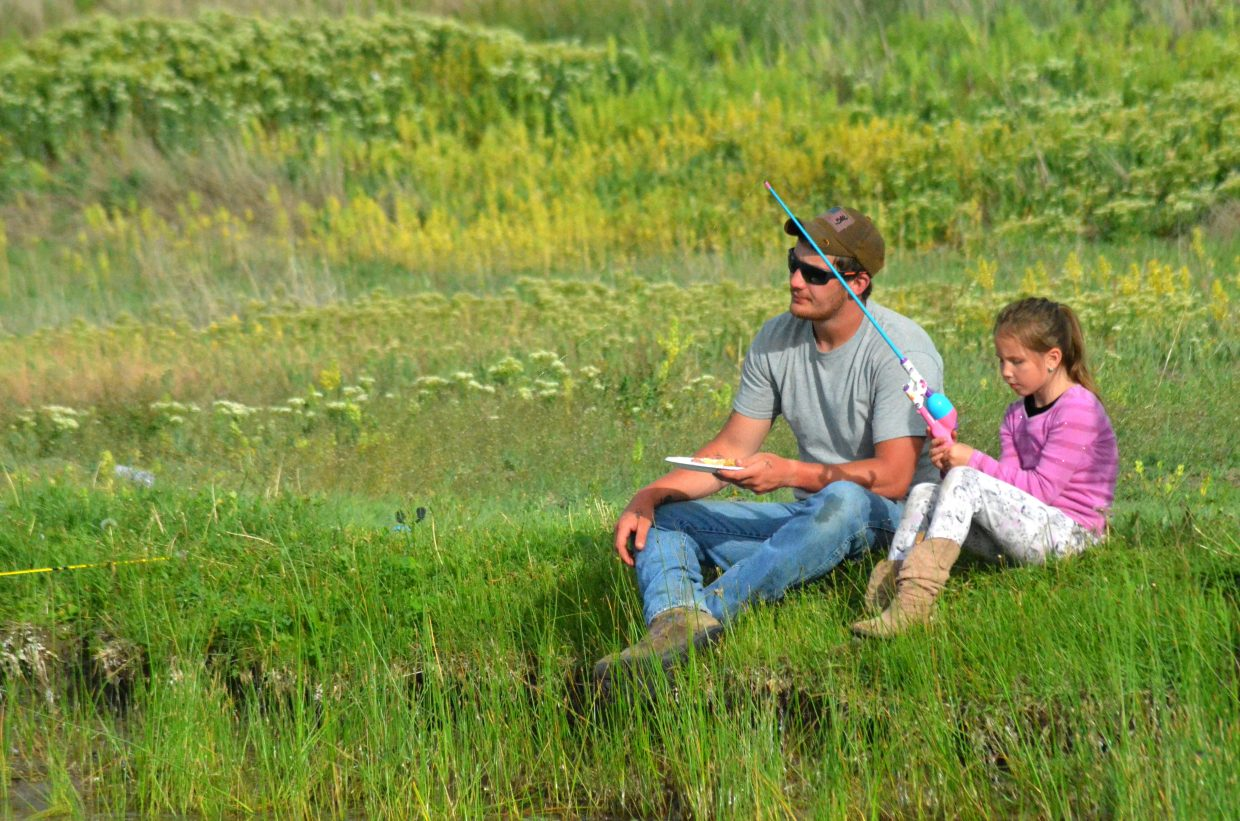 Jordan Walker and daughter Riley take it easy by the side of Little Rascals Pond during Cops, Kids and Vets Fishing Day.