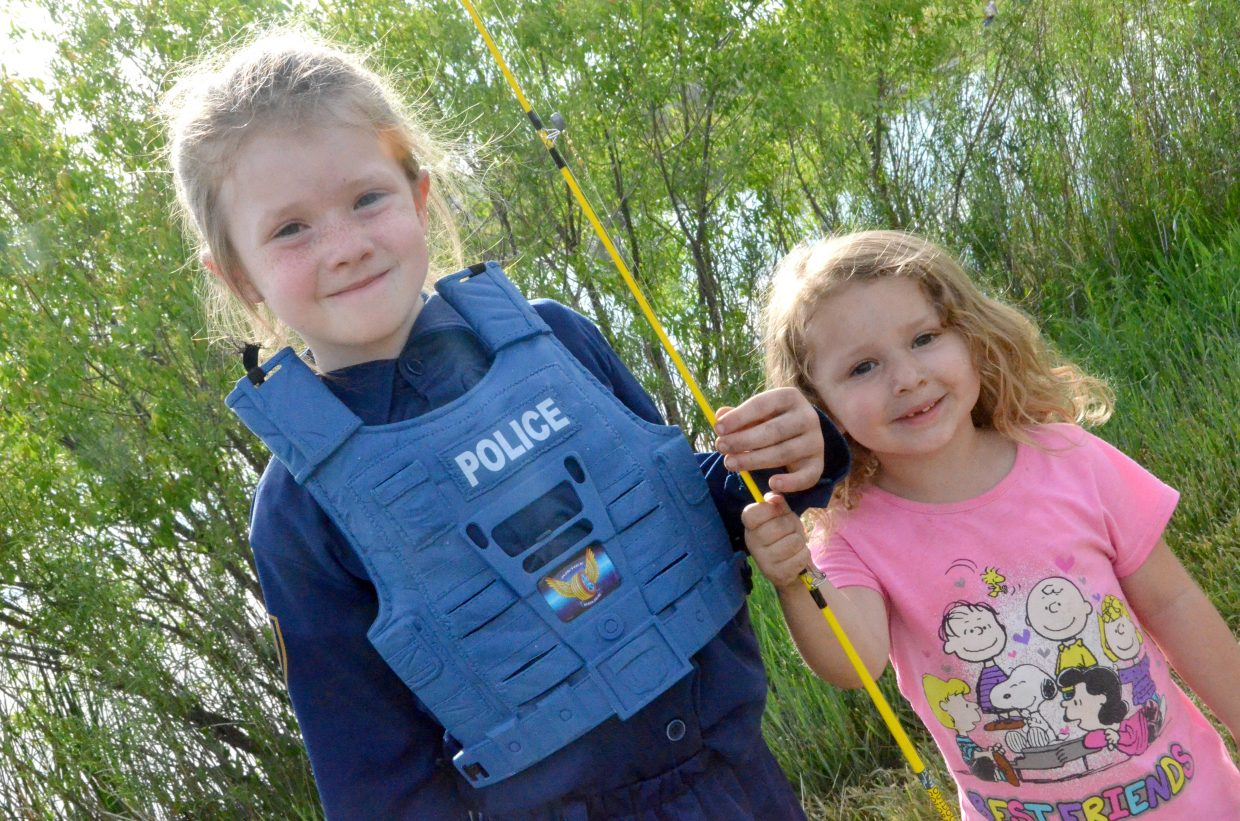 Allie King, left, and Kinley Peters share a pole during 2018's Cops, Vets and Kids Fishing Day.