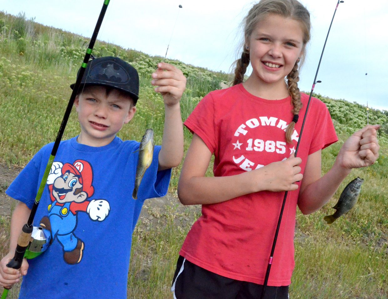 Siblings Maks and Taryn Schlim hold up their fishes caught during Cops, Kids and Vets Fishing Day.