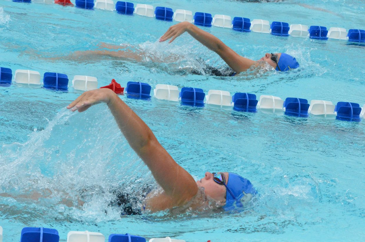 Teammates Kelsey McDiffett, top, and Katelynn Turner stay synced in the 200 backstroke during Craig Sea Sharks Open Swim Meet Saturday at Craig Pool Complex.