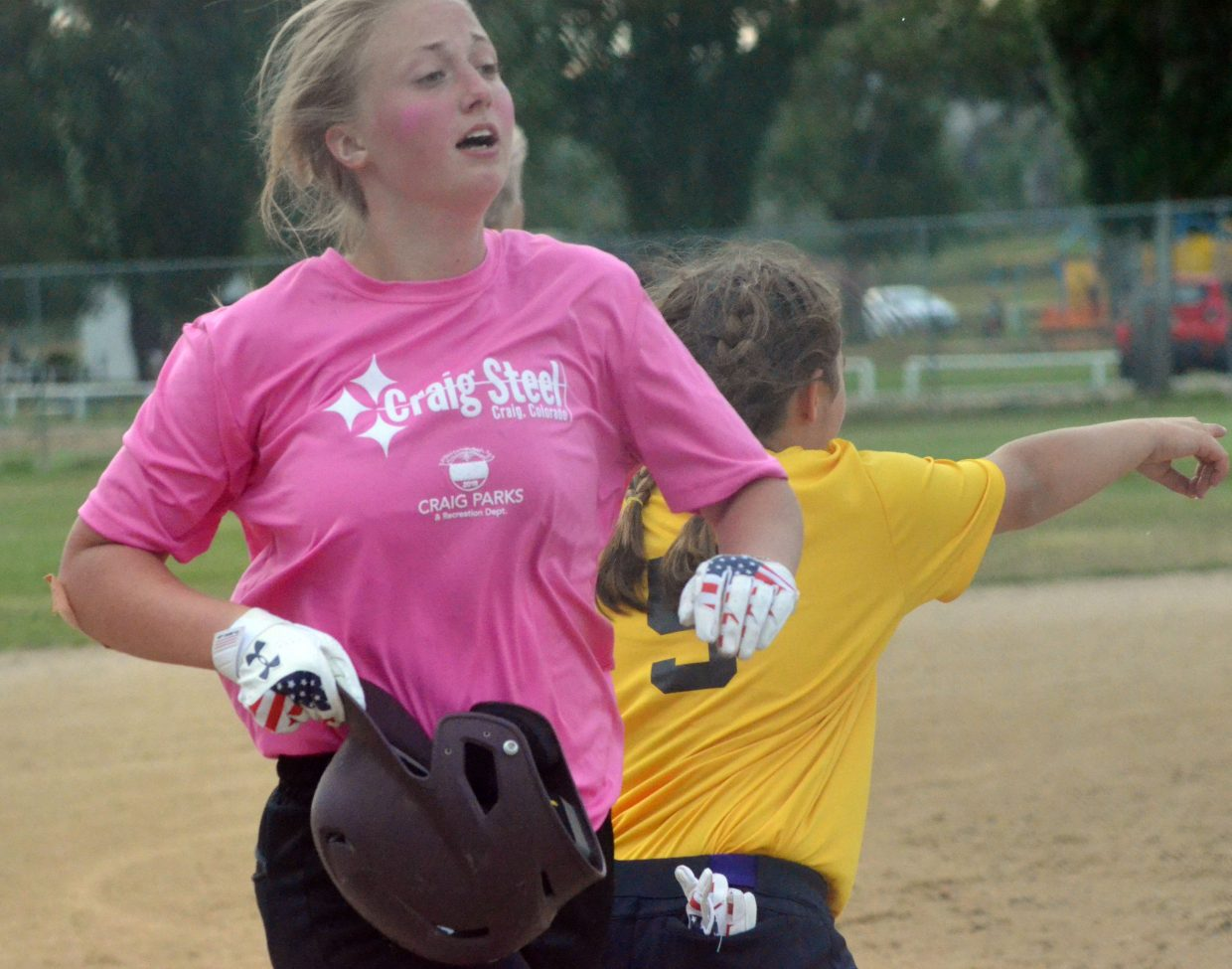 Craig Steel's Justice McMillan rips off her batting helmet as she crosses home plate.