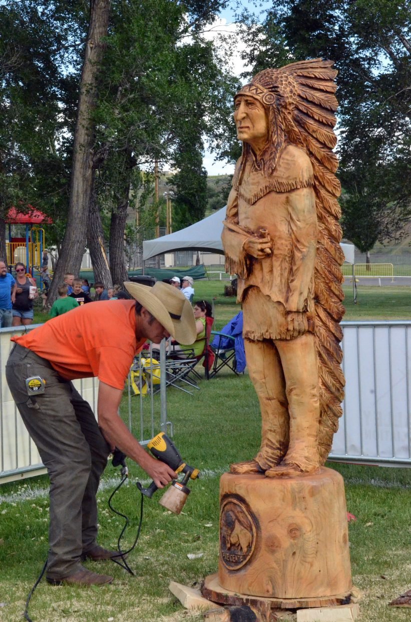 Doug Moreland puts some finishing touches on his carving of a Native American Friday during the 19th annual Whittle the Wood Rendezvous at Loudy-Simpson Park.