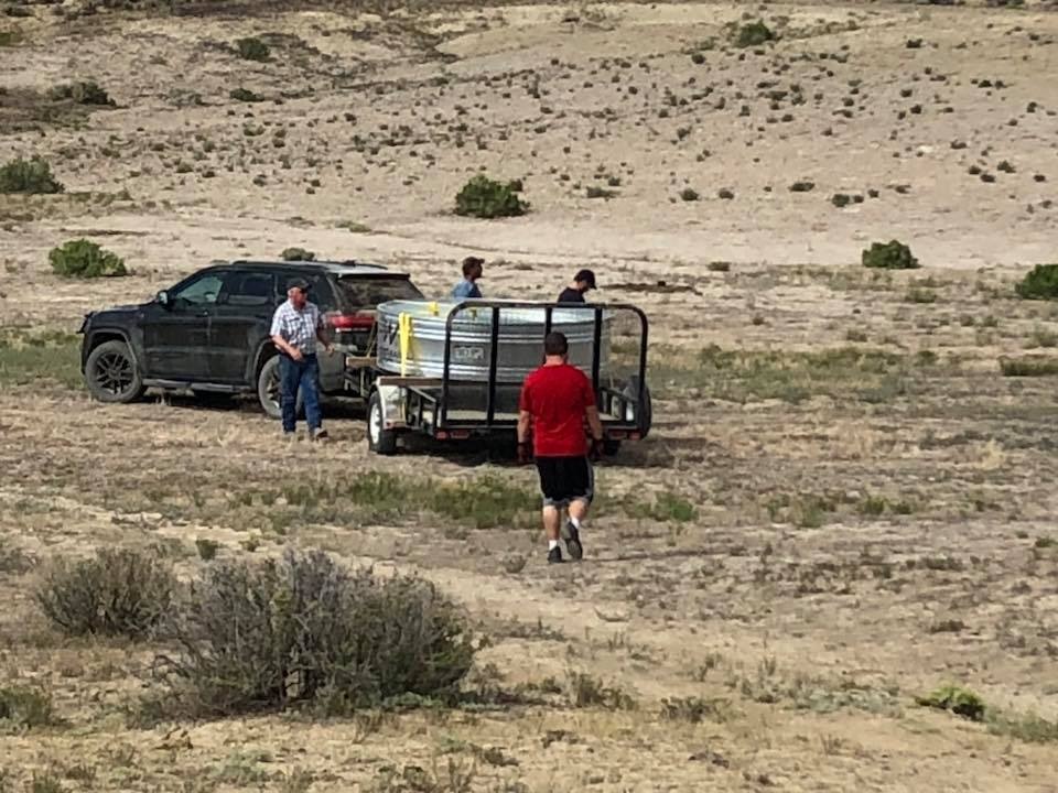 Ernie Wright, and his sons Jon, Joe and Rocky Wright prepare to unload one of three stock tanks being used by volunteers.