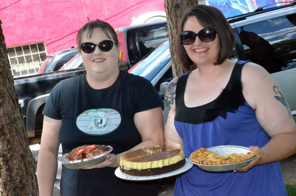Aubrey Wilkey, left, and Kassie Vesely hold up their winning pies following the baking contest hosted by Downtown Business Association. Wilkey won Best Cream Pie and Vesely Best Fruit Pie and Best Cheesecake.