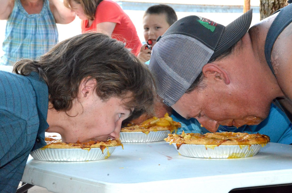 Brandon Madsen, left, and Eli Vesely go head to head during the pie-eating contest hosted by Downtown Business Association. Madsen won the adult's division.