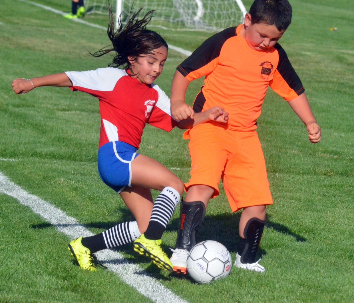 Natalia Quezada of the Fire, left, battles for the ball with Caleb Bennett of the Earthquakes during a Craig Parks and Recreation 8 and under soccer game. The league finishes its season Thursday.