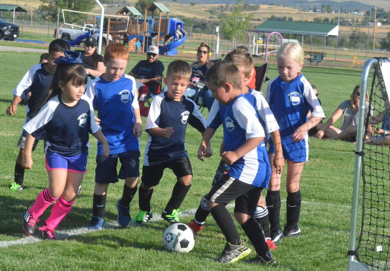Players with the Bulldogs and Tornados swarm the ball during a Craig Parks and Recreation 6 and under soccer game.
