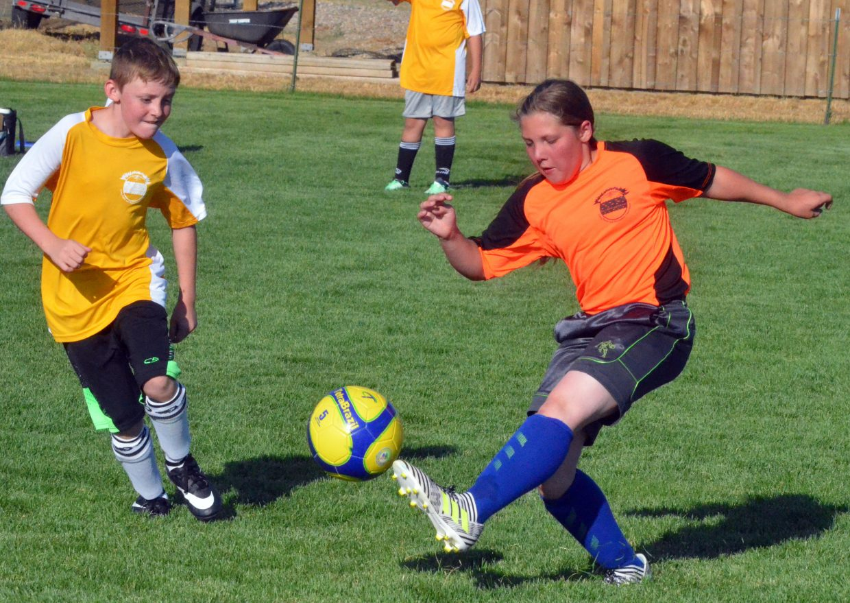 The Outlaws' Timmy O'Neal, left, gets moving as the Fusion's Abby Martinez gets her toe on the ball during a Craig Parks and Recreation 12 and under soccer game.