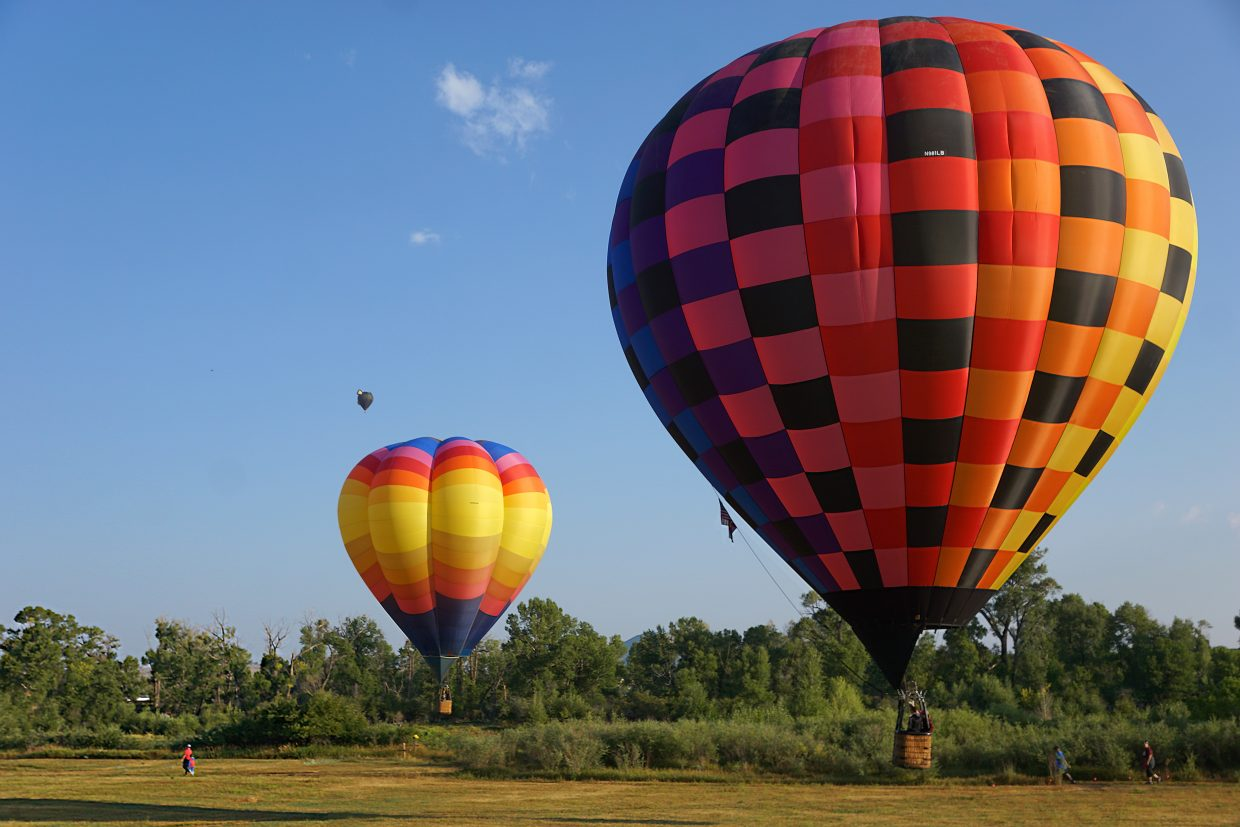 Runners in the Elevate Education 5K race below hot air balloons during Moffat County Balloon Festival.