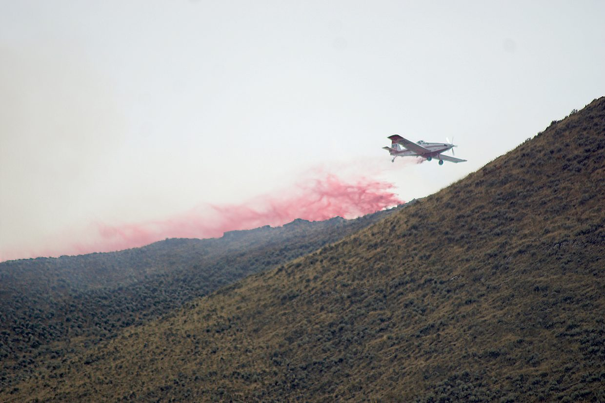 A plan dumps slurry on a 5-acre fire that started on Cedar Mountain, about 7 miles Northwest of Craig, Monday evening.