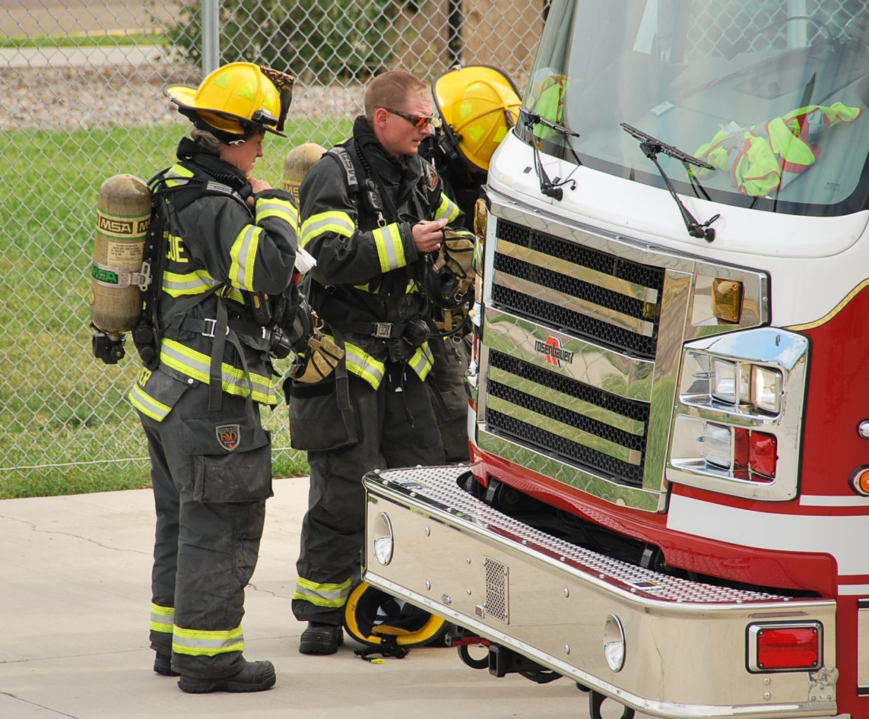 Craig firefighters gear up and check each others equipment before performing a rescue.