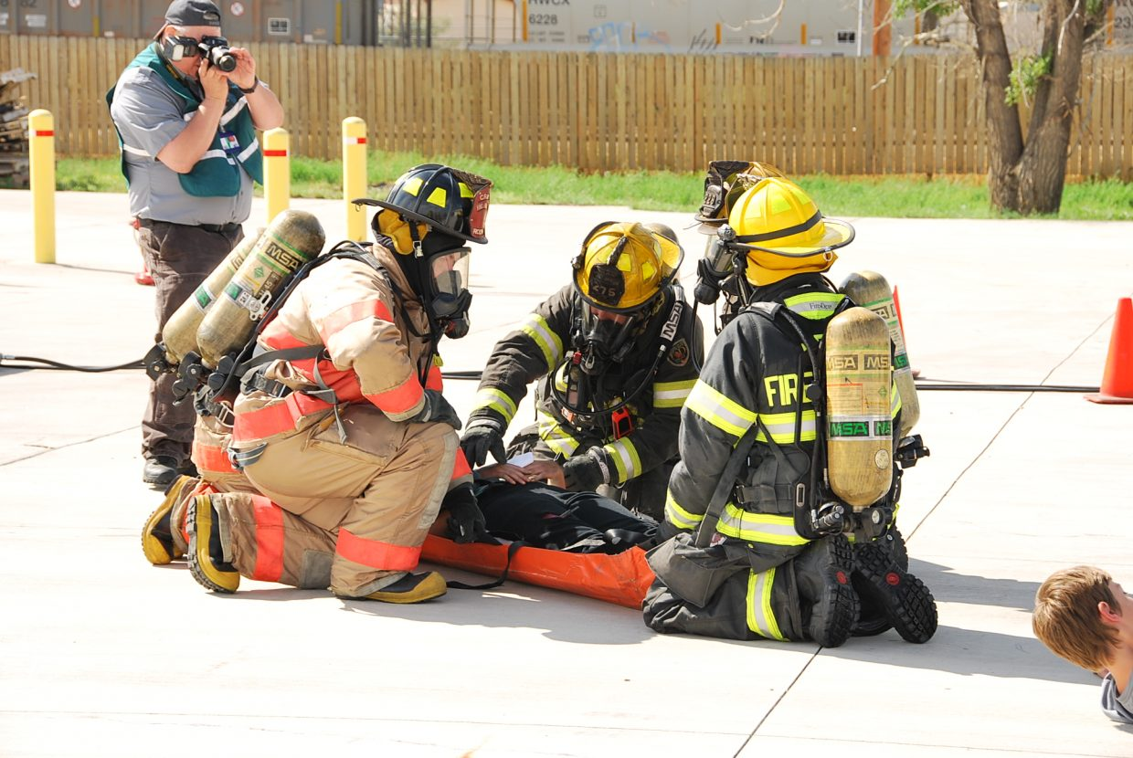 A victim is loaded onto a stretcher to be carried to safety.