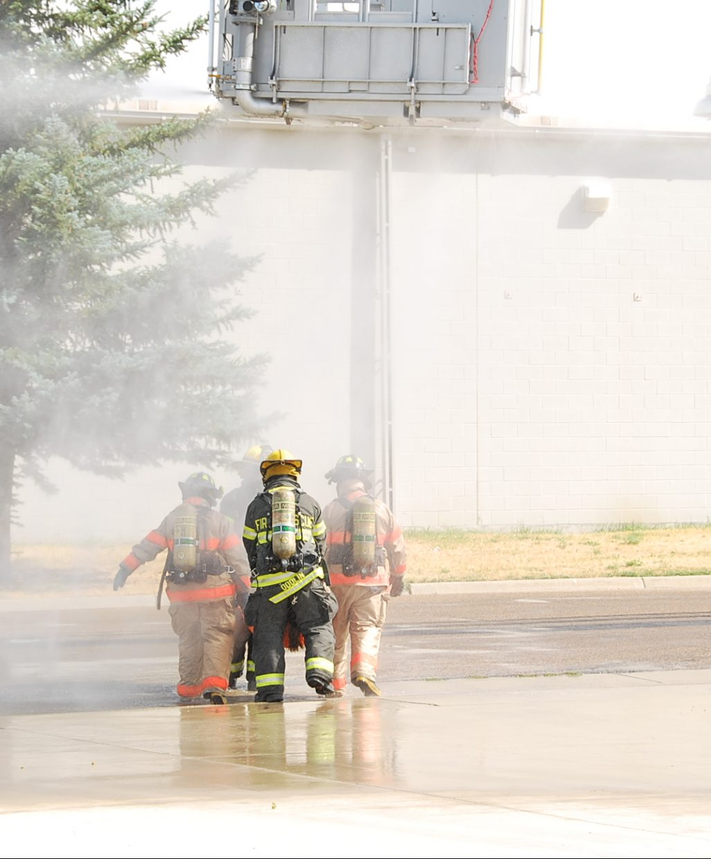Firefighters walk through the decontamination shower with a victim as part of the training.