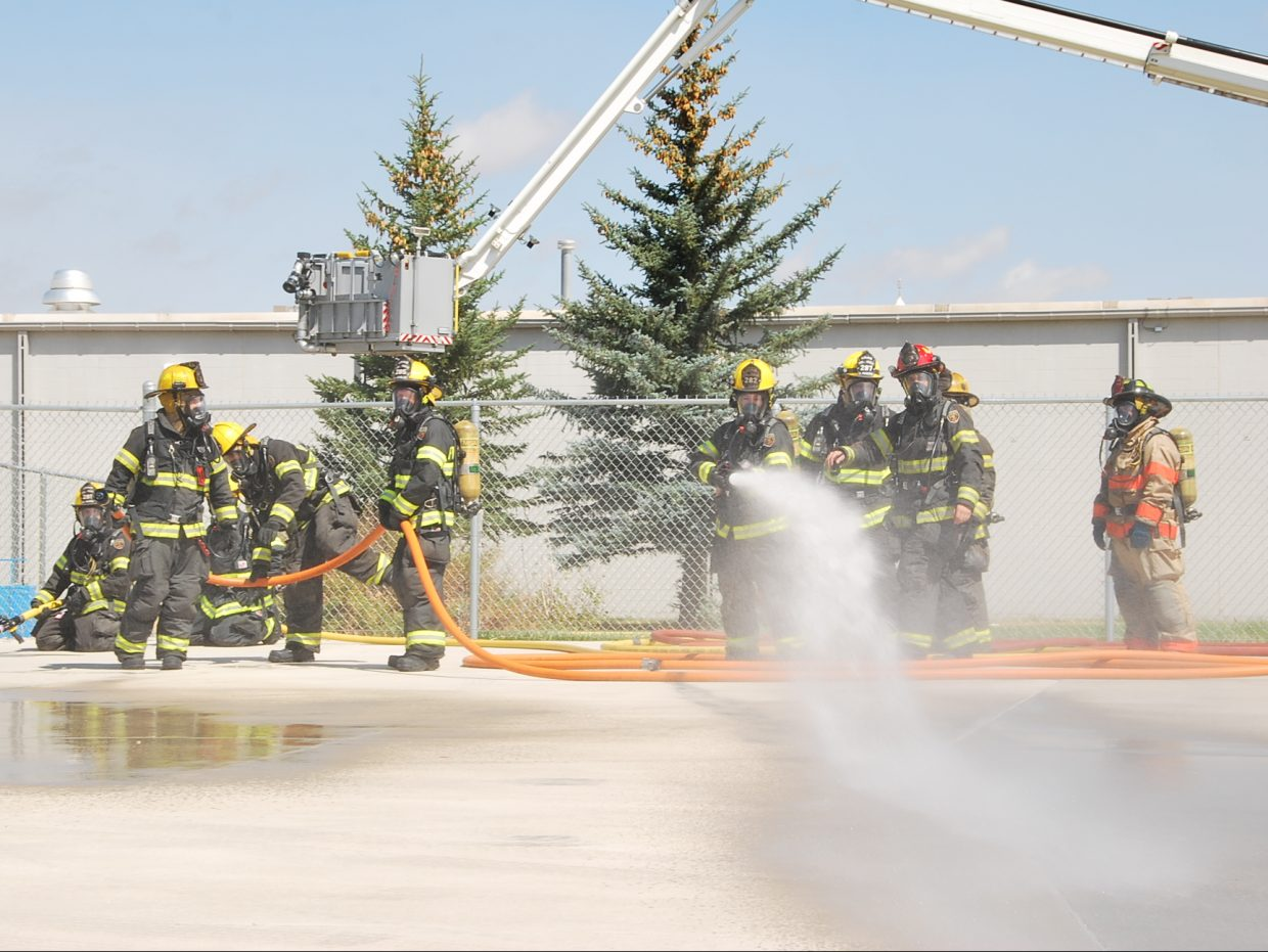 A firefighter tests a hose before putting it to use.