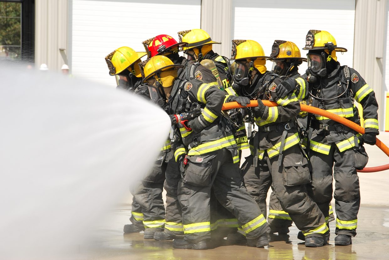 A firefighting team approaches a fire to contain it. This exercise was to simulate an open valve fire from a gas line.