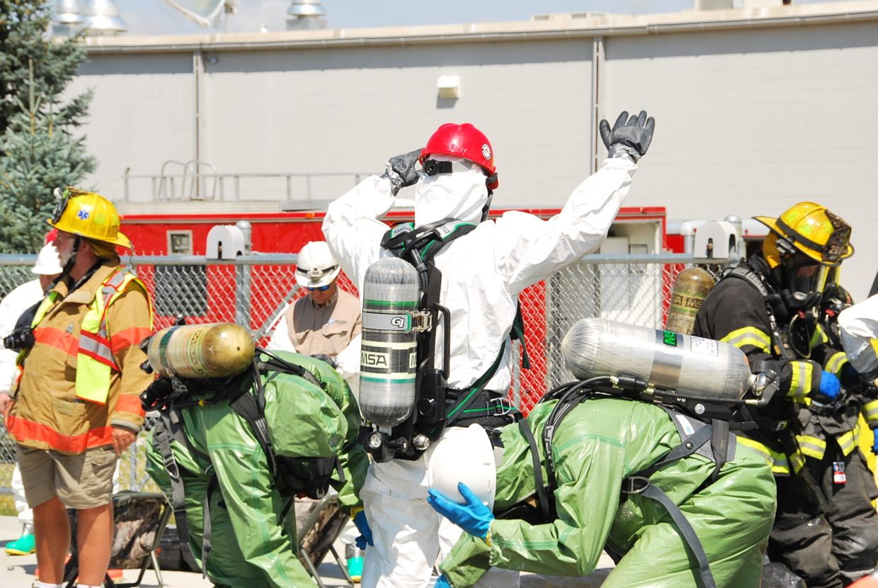 A Haz-Mat team member is scrubbed down by fellow team members.