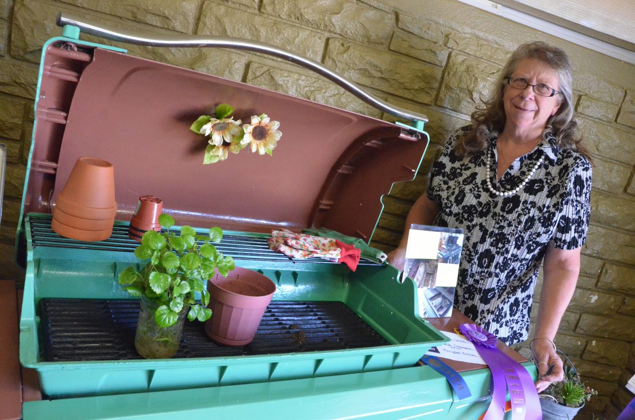 Maria Witts displays her fair entry, a barbecue remade as a yard decoration, in the pavilion of Moffat County Fairgrounds.