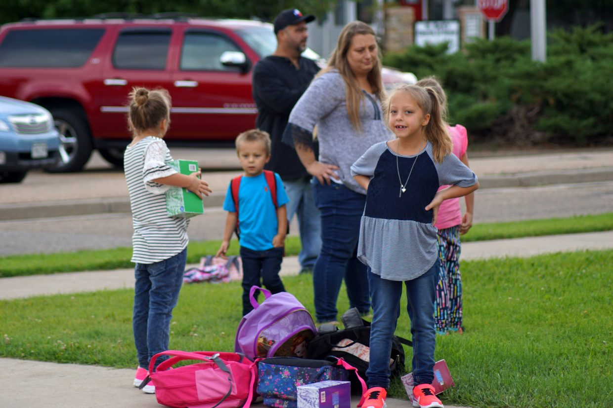 Kaylah Hodgkinson waits with her family to pose for a first day of school photo. Kaylah and her sisters, Ruby and Savannah, are triplets. Their younger brother, Liam, in the blue shirt, is not yet in grade school.