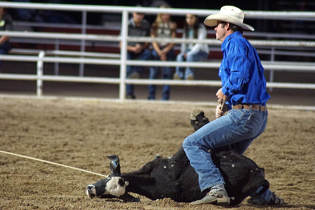 A cowboy signals he's done during the tie-down competition.