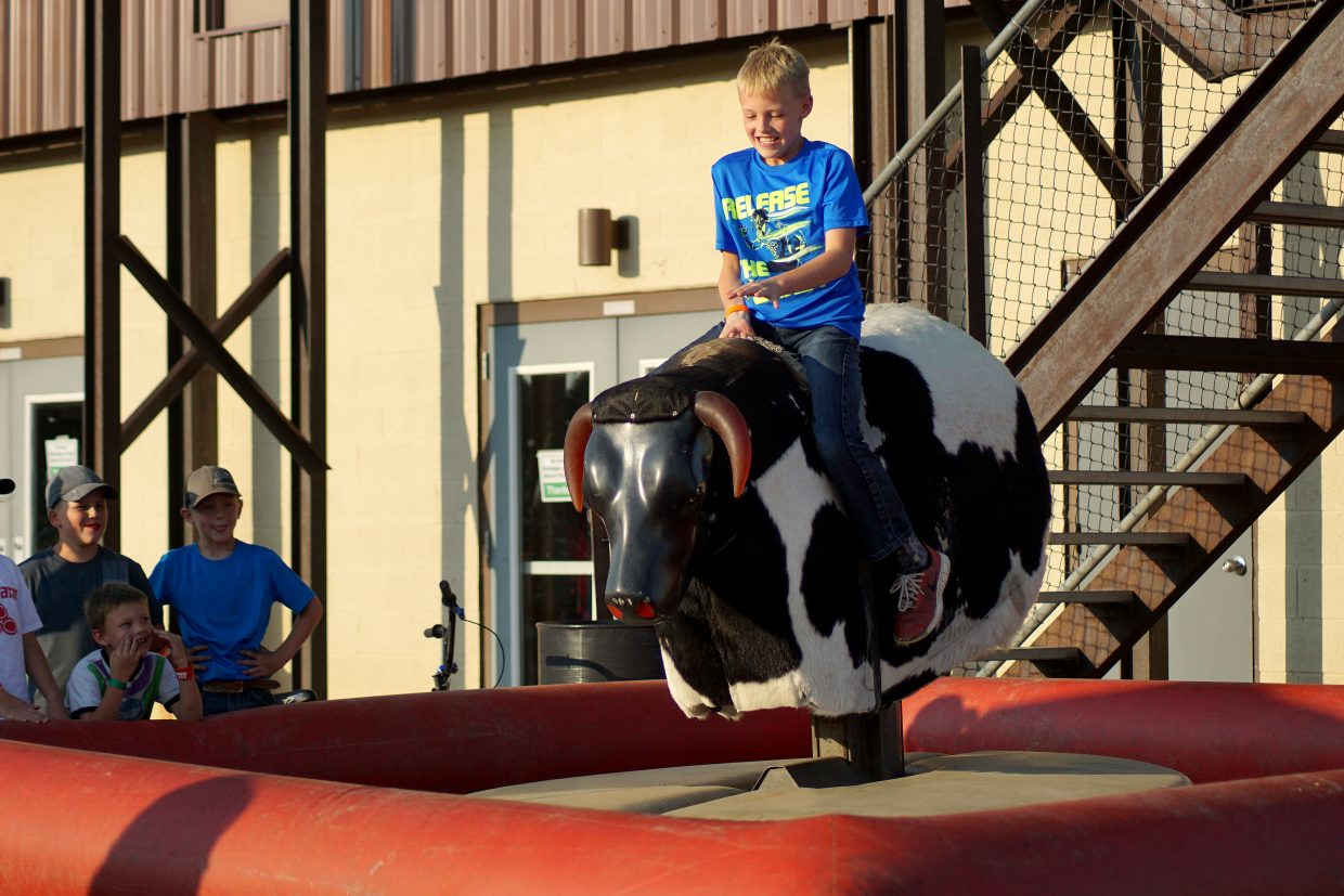 Bullrider in the making? A young man tries his hand on the mechanical bull before the start of the pro rodeo.