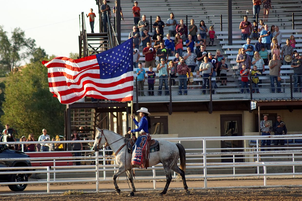 The American flag, carried by Miss Rodeo Colorado Alex Hyland, passes in front of the grandstands Thursday evening.