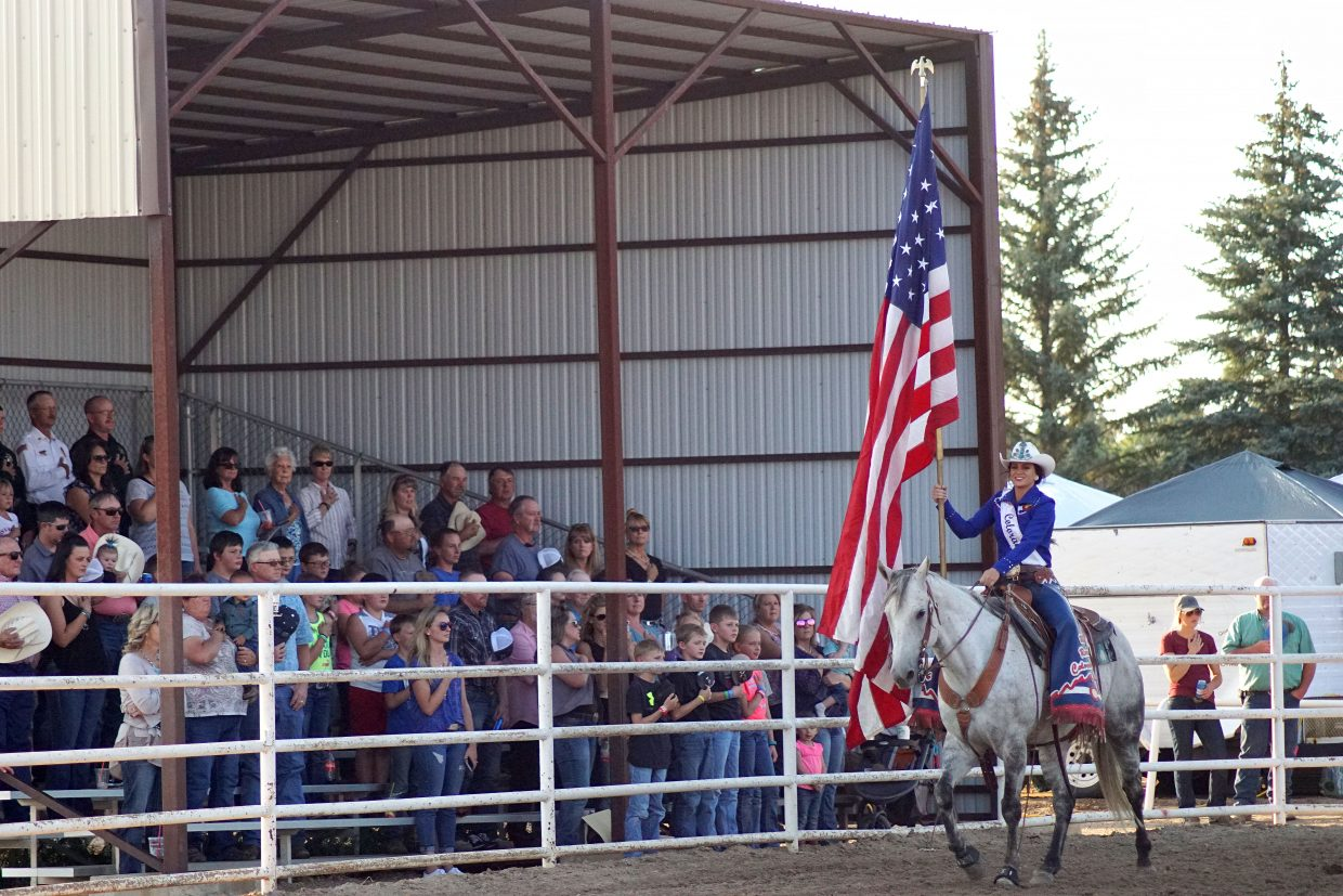 Miss Rodeo Colorado Alex Hyland proudly carries the American flag as spectators pause to salute.