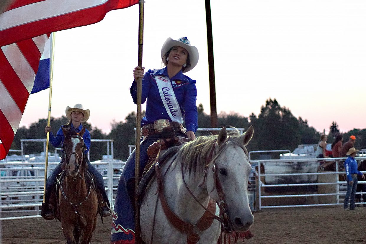 Miss Rodeo Colorado Alex Hyland proudly carries the American flag, as local rodeo royalty rides behind her, carrying the flag of Colorado.
