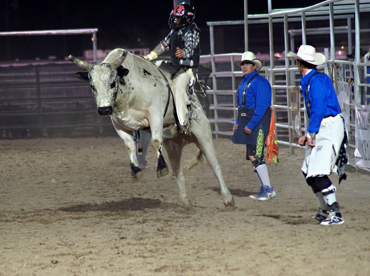 A bull leaps and twists to unseat a rider.