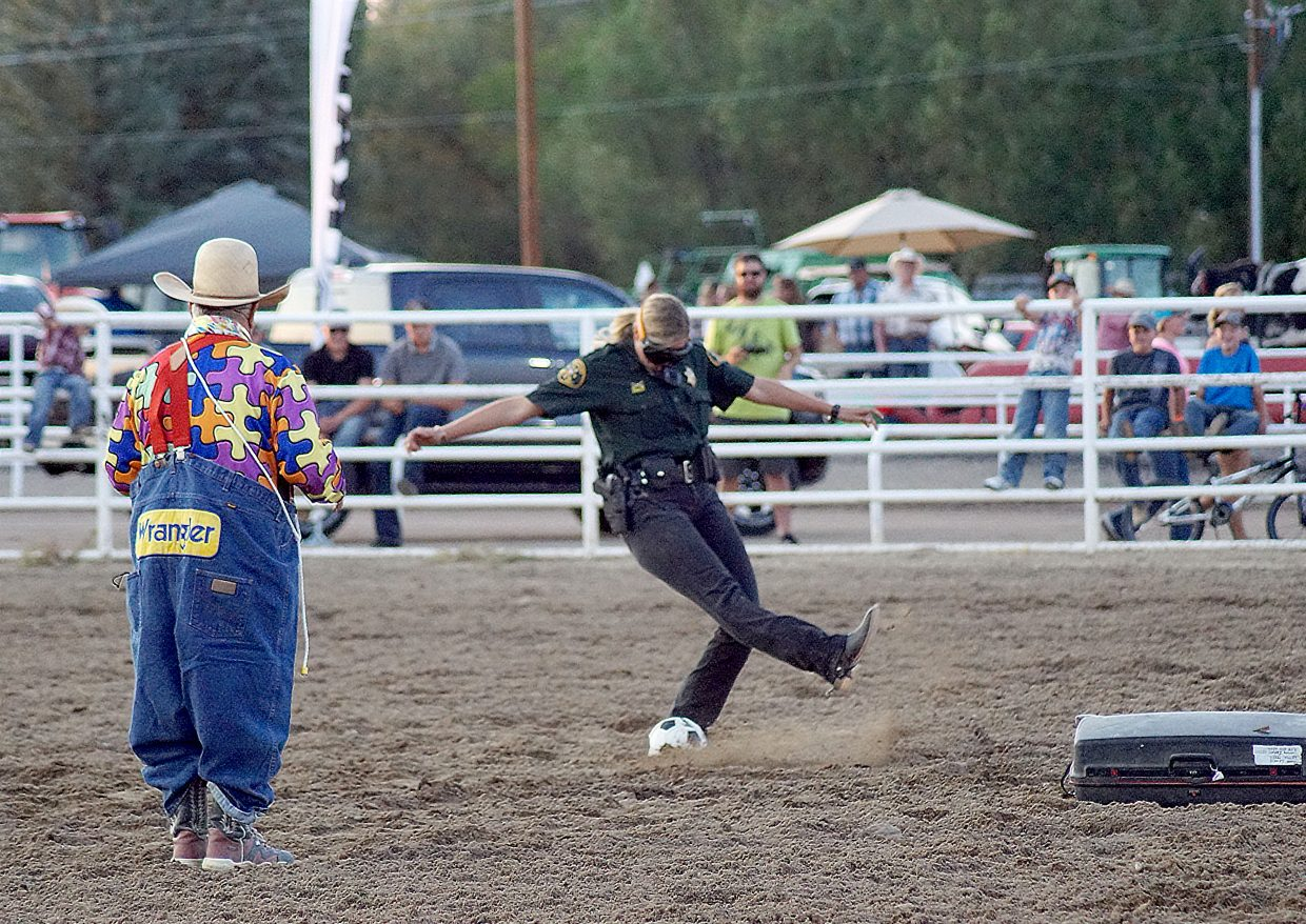 A sheriff's deputy — wearing goggles that simulate the vision of a person who is over the legal blood alcohol limit —  attempts, and fails, to kick a soccer ball. The demonstration helped clown Donnie Landis remind the crowd why it's not a good idea to drink and drive.