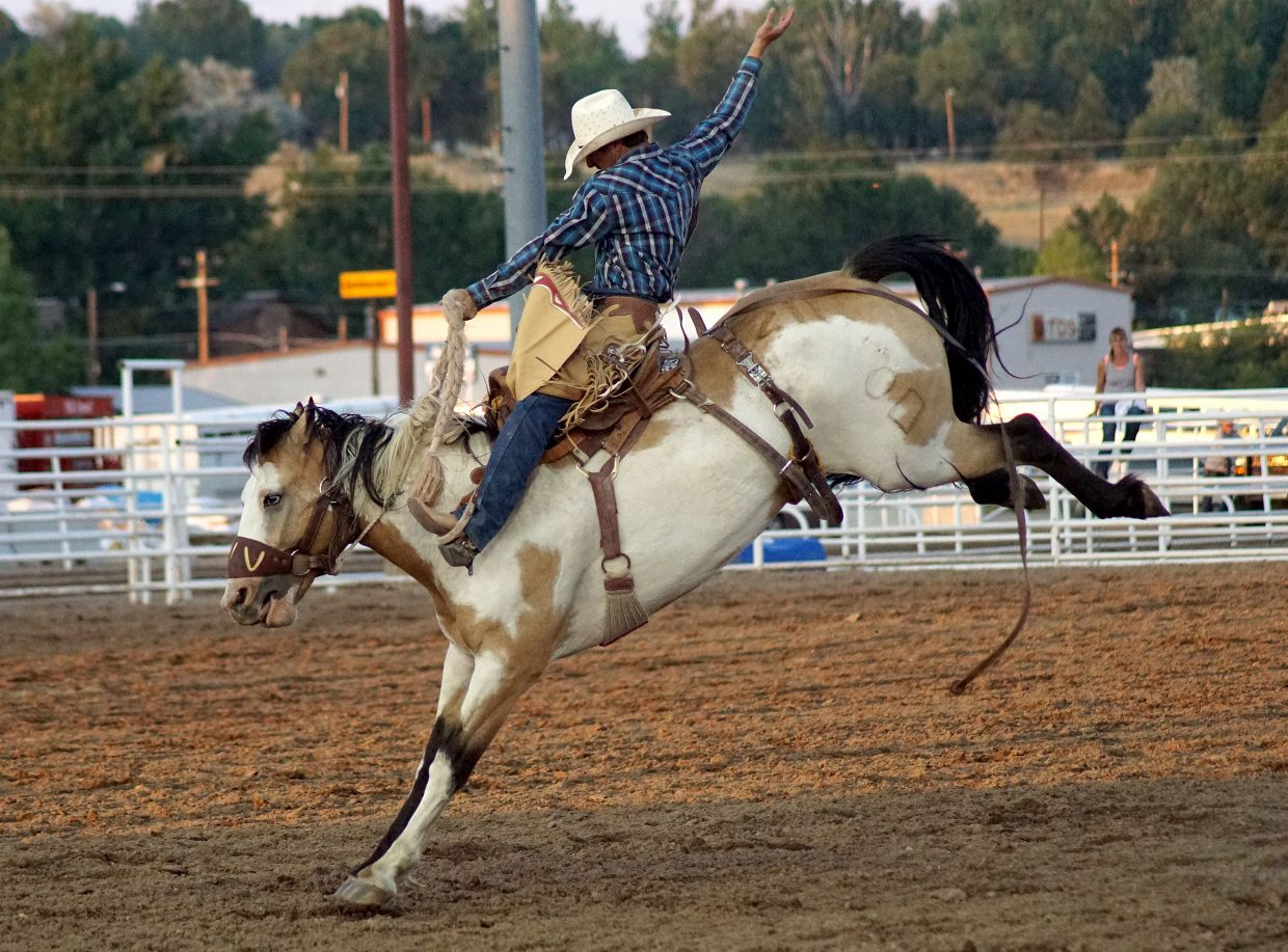A saddle bronc rider reaches high to keep his balance on a horse determined to unseat him.