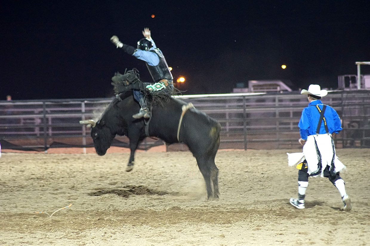 A cowboy clings to the back of a bull working hard to throw him off.