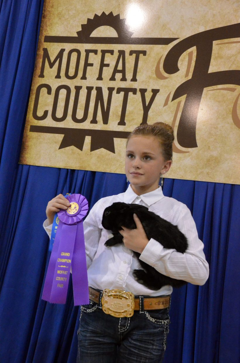 Kayla Deaton and Summer display their grand champion ribbon for the rabbit show Friday at the Moffat County Fair.