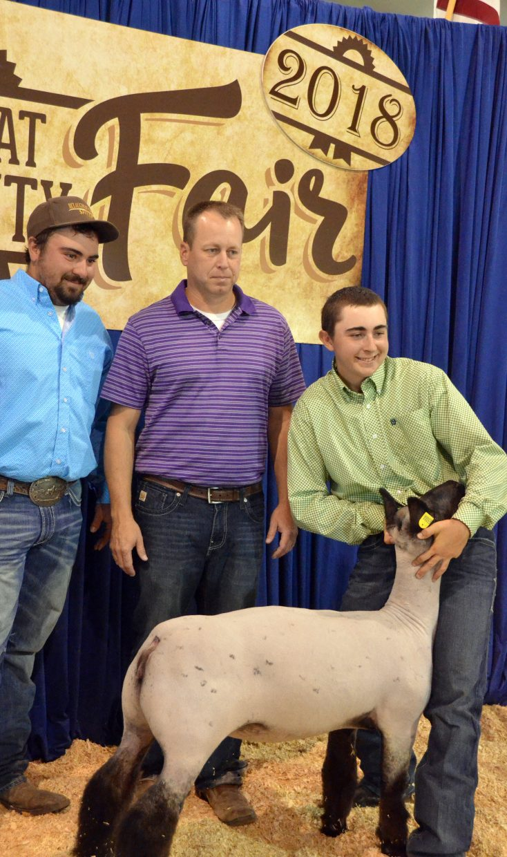 Dustin McLaughlin grabs a championship photo with his winning breeding ewe at the Wednesday sheep show at the Moffat County Fair.