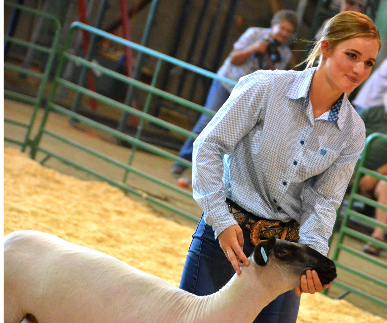 Payton Voloshin smiles following a successful showing during the market class division of the Wednesday sheep show at the Moffat County Fair.