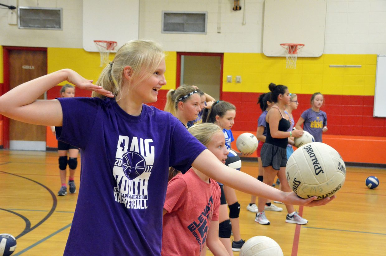 Hannah Crookston grins as she lines up a serve during a serving drill at the Parks and Recreation Volleyball Camp at Sandrock Elementary School.