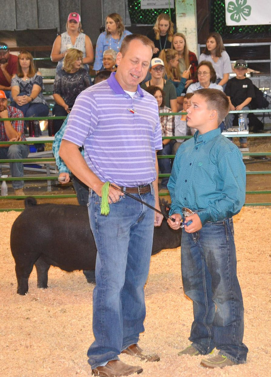 Cashton Counts, right, talks with Judge Bill Disberger during the intermediate showmanship division of the swine show at the Moffat County Fair on Friday.