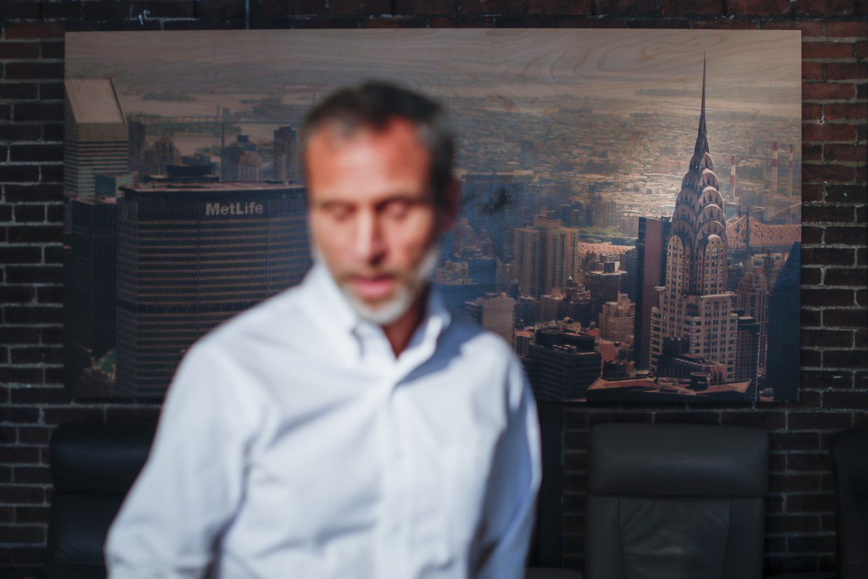 Michael Koveleski, is interviewed in the showroom of their store Design Sleep where an aerial photograph of the Chrysler Building hangs on their wall in Yellow Springs, Ohio on Thursday, Aug. 23, 2018. He and his wife, Margery, left New York in the wake of 9/11 with four children and no work lined up. (AP Photo/John Minchillo)