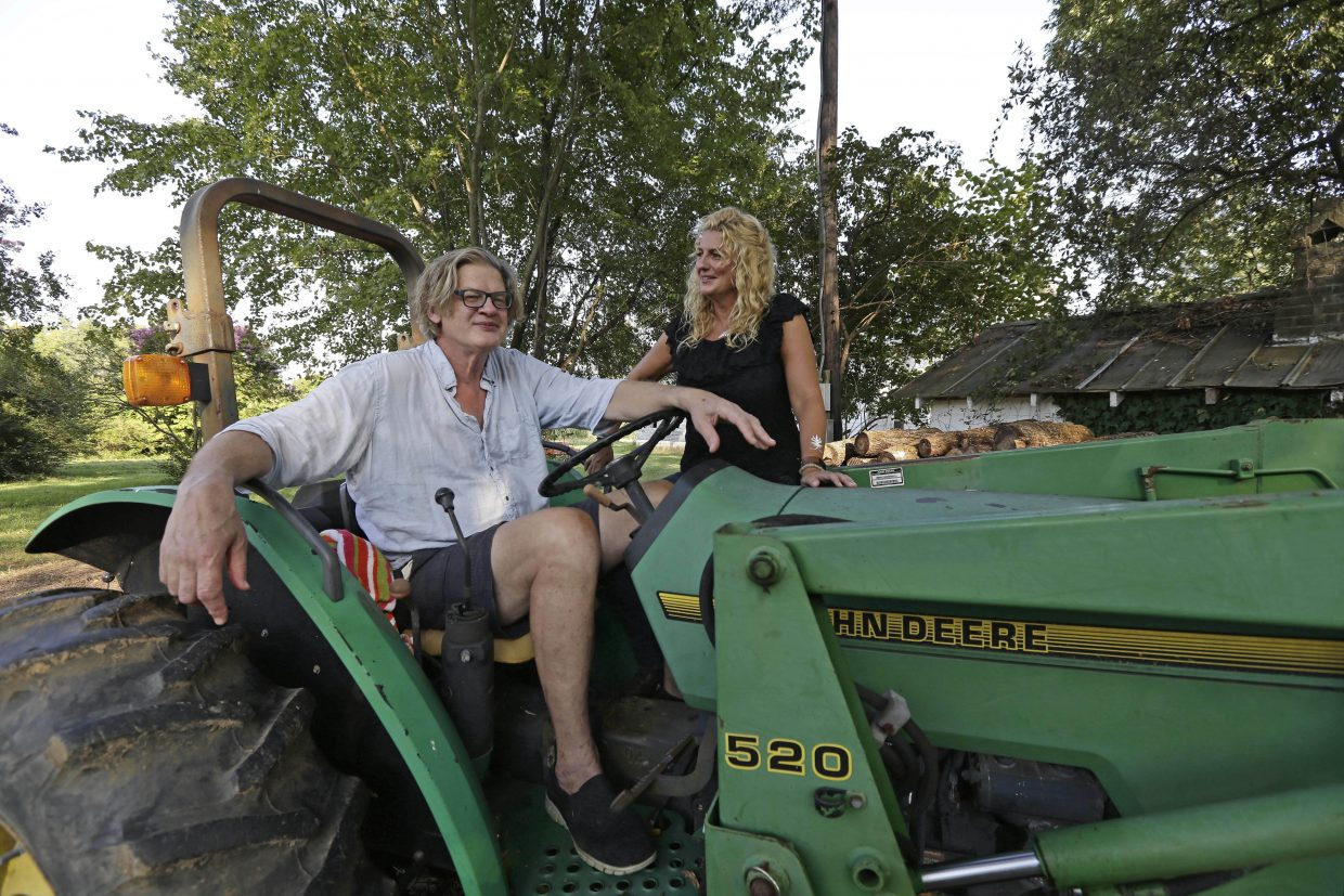 Tom and Heather LaGarde are seen on Tom's tractor at their home near Saxapahaw, N.C., on Wednesday, Aug. 29, 2018. The LaGardes left New York following the events of 9/11.