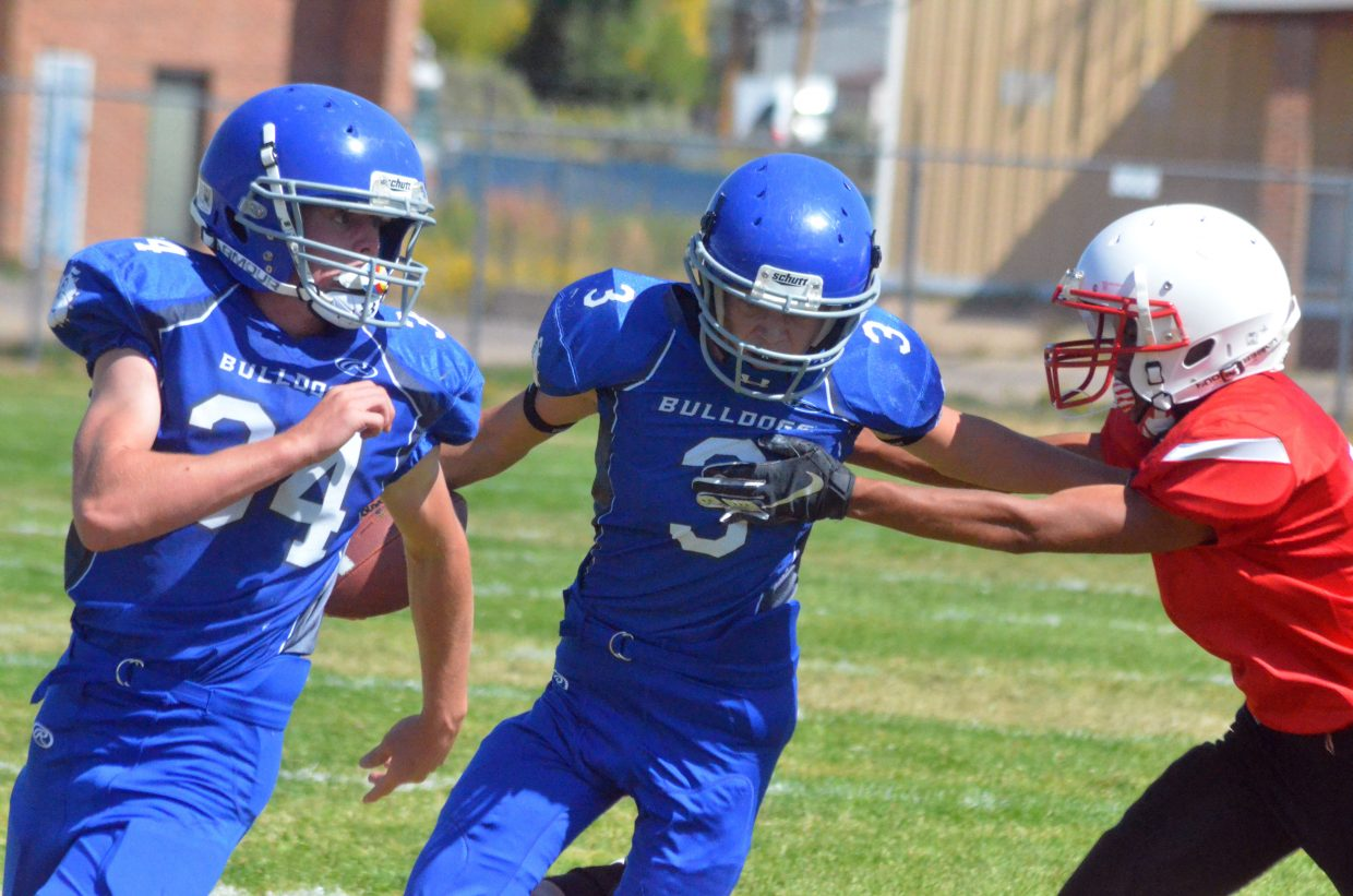 Craig Middle School's Chayton McDonald stays in blocking mode while Cort Murphy stiff-arms Rawlins defenders.