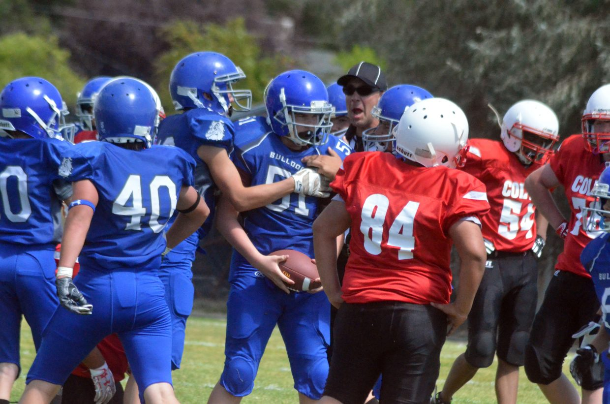 Craig Middle School eighth-grade football players swarm teammate Jud Grims after a fumble recovery against Rawlins.