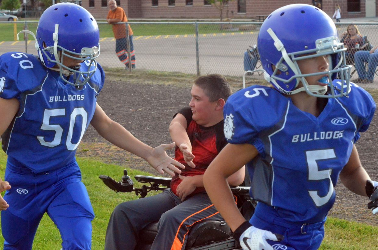 Craig Middle School's JP Price exchanges high-fives with football players as they prepare for their game against Meeker.