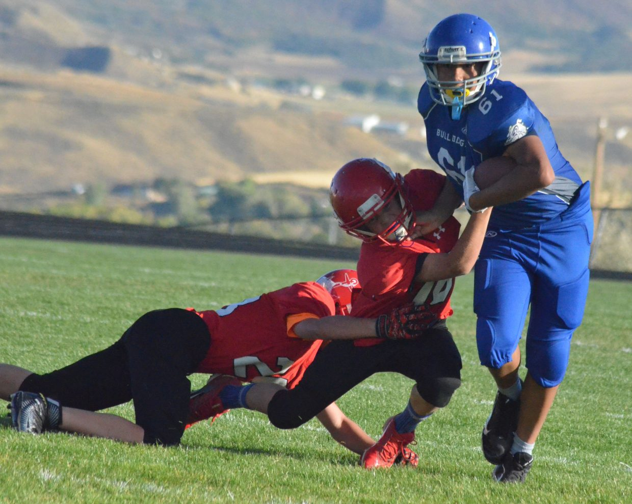 Craig Middle's School's Alexis Barraza drags along Steamboat Springs defenders while making a rush.