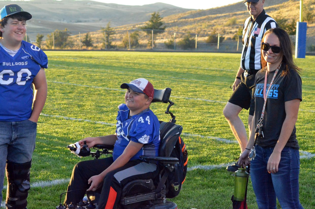 Craig Middle's School's Garrett Anson and JP Price joke around with CMS Athletic Director Sara Linsacum during the Bulldogs' football game with  Steamboat Springs.