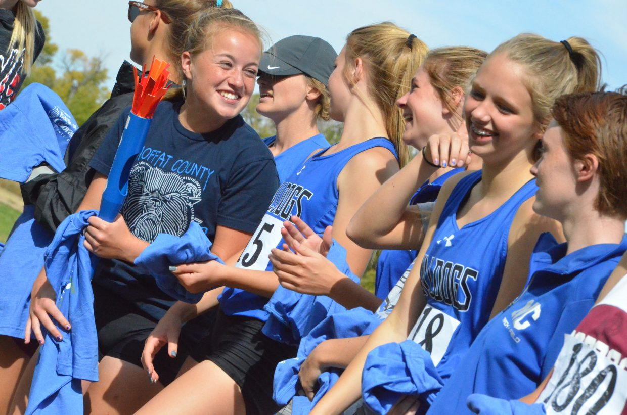 The Moffat County High School girls cross country team shares a laugh during the awards ceremony at Saturday's MCHS Invitational. Moffat County boys and girls teams won the home meet.