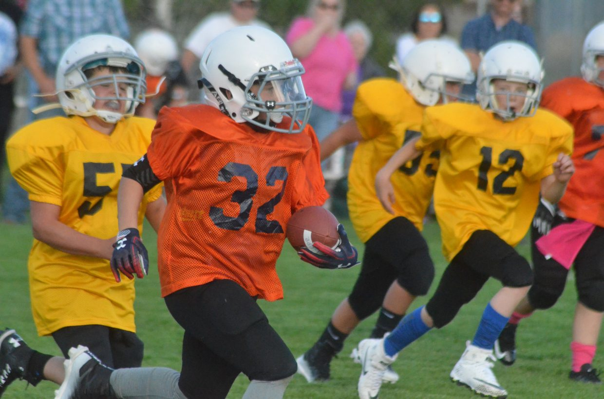 The Broncos' Hayden Urroz scrambles for yardage against the Steelers during a Doak Walker fifth- and sixth-grade game.