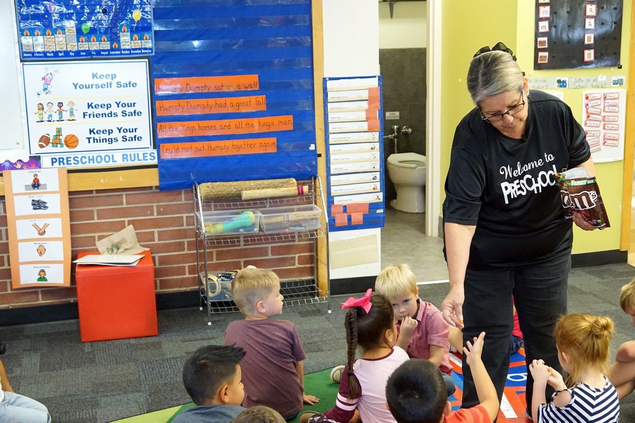 Preschool teacher Mary Ginther gives sweet treats to her