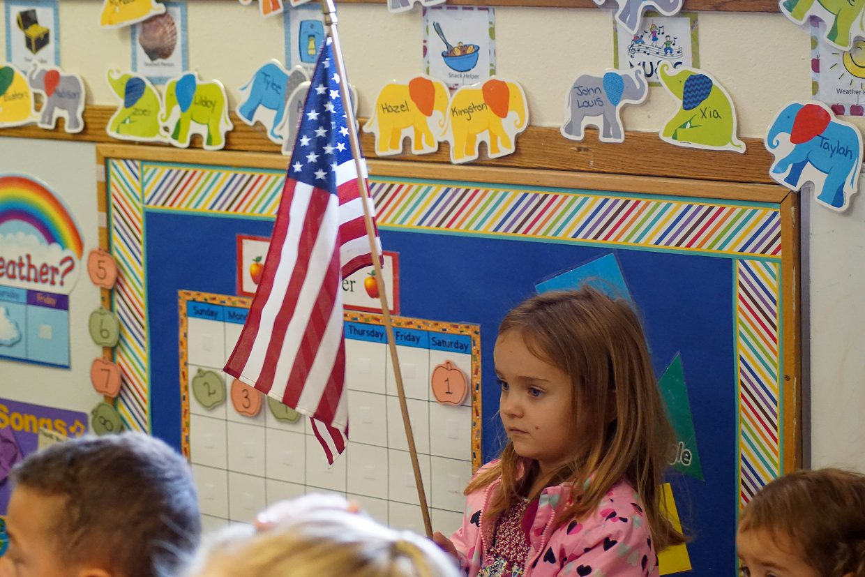 Zoei Bailey holds the American flag during circle time at Eagle's Nest Preschool — which is celebrating 12 years. The children's day starts with the pledge to the flag and Bible.