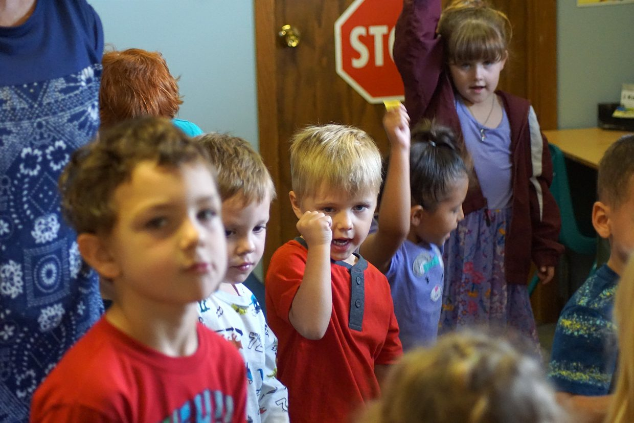Children stand for pledges and morning songs. Brody Swartz as does Irene Peck, behind him in purple.