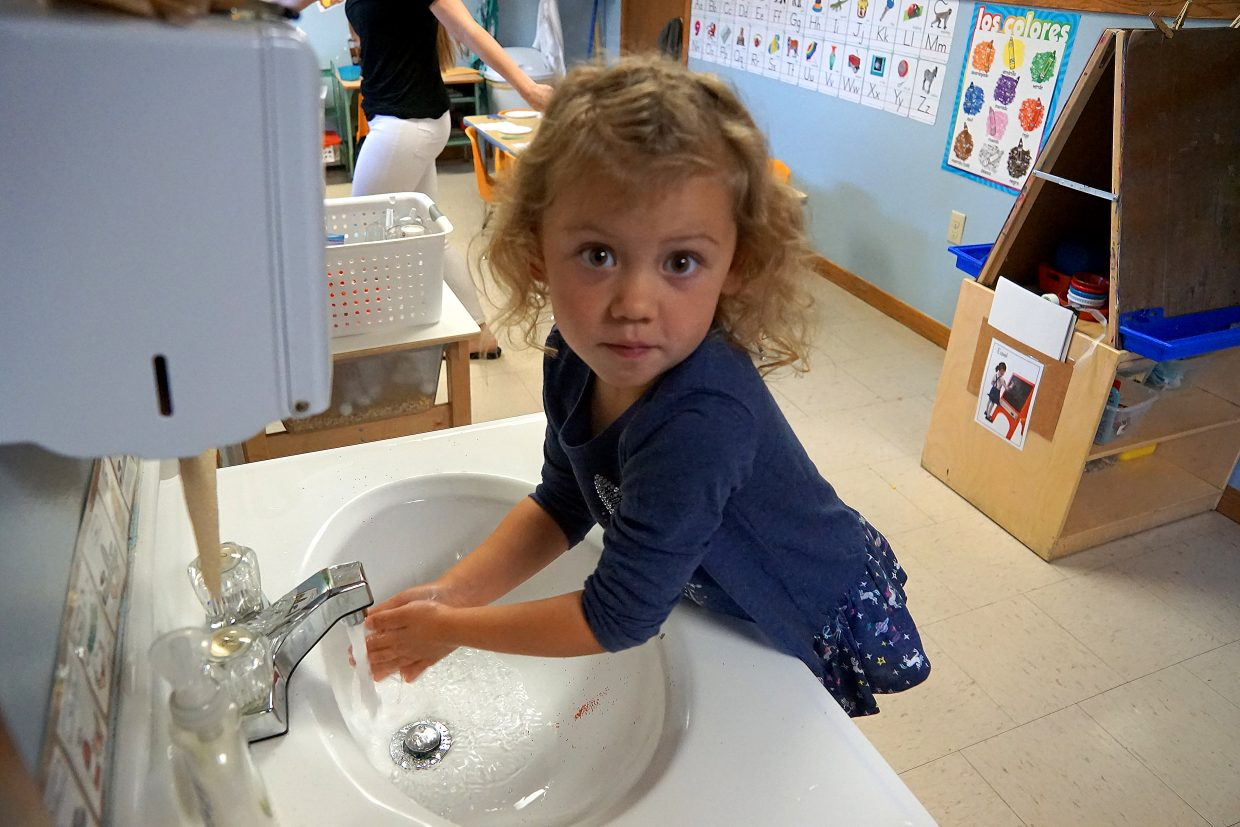Preschooler Ava Myers washes her hands after instruction about the importance of removing germs before snack time.
