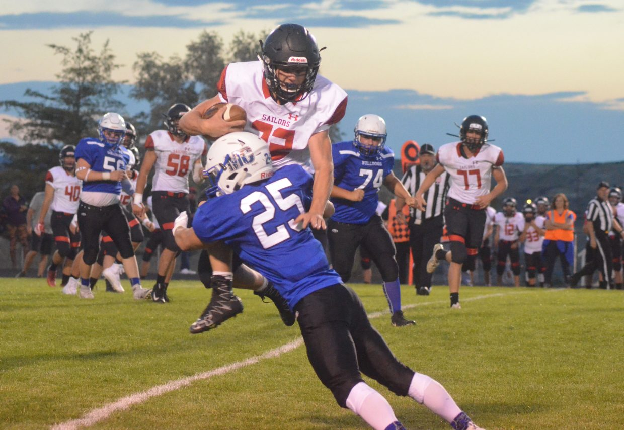 Steamboat Springs' Austin Ban attempts to vault for some extra yardage only for Moffat County High School's Josh Teeter to deny him. MCHS beat the Sailors 21-14 Friday night.
